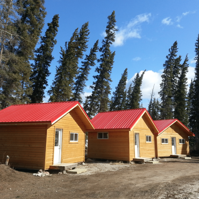 visual image of red metal roofs on three small buildings